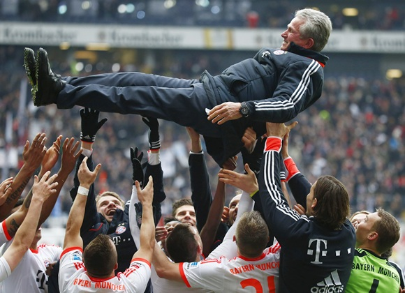 Bayern Munich's players throw coach Jupp Heynckes in the air