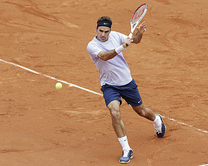 Roger Federer of Switzerland hits a return to Pablo Carreno-Busta of Spain during their first round match of the French Open at the Roland Garros on Sunday
