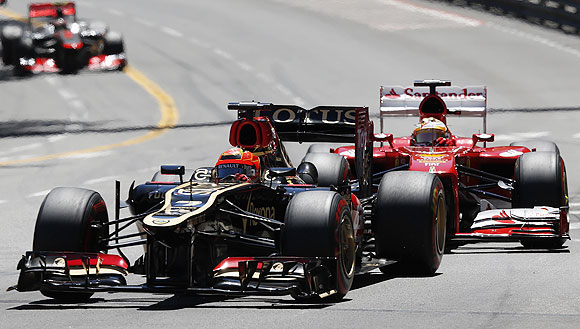 Lotus Formula One driver Kimi Raikkonen (left) steers his car ahead of Ferrari's driver Fernando Alonso during the Monaco F1 Grand Prix on Sunday