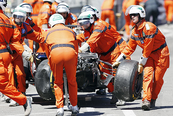Safety personnel remove the wrecked car of Williams Formula One driver Pastor Maldonado after a crash, during the Monaco Grand Prix on Sunday