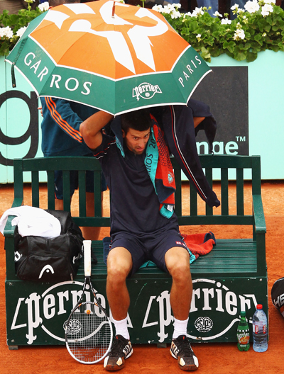 Novak Djokovic of Serbia shelters from the rain during the men's singles final against Rafael Nadal of Spain at Roland Garros on June 11, 2012