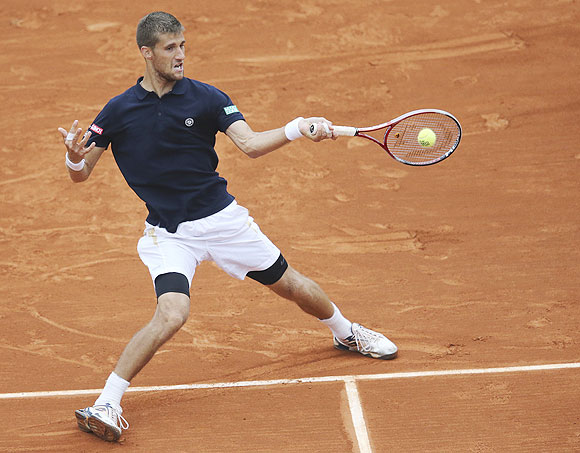 Martin Klizan of Slovakia hits a return to Rafael Nadal