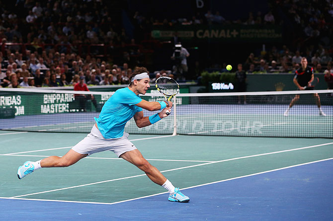 Rafael Nadal of Spain stretches to play a backhand against Jerzy Janowicz of Poland during the BNP Paribas Masters at Palais Omnisports de Bercy in Paris on Thursday