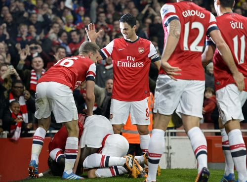 Arsenal players celebrate after winning a team