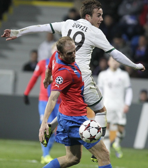 Viktoria Plzen's Roman Hubnik (front) fights for the ball with Bayern Munich's Mario Goetze