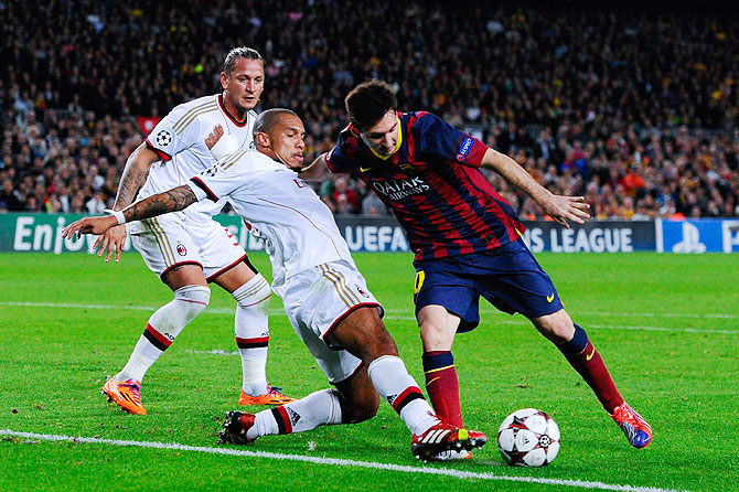 Lionel Messi of FC Barcelona duels for the ball with Nigel de Jong of AC Milan during the UEFA Champions League Group H match at Camp Nou in Barcelona on Wednesday