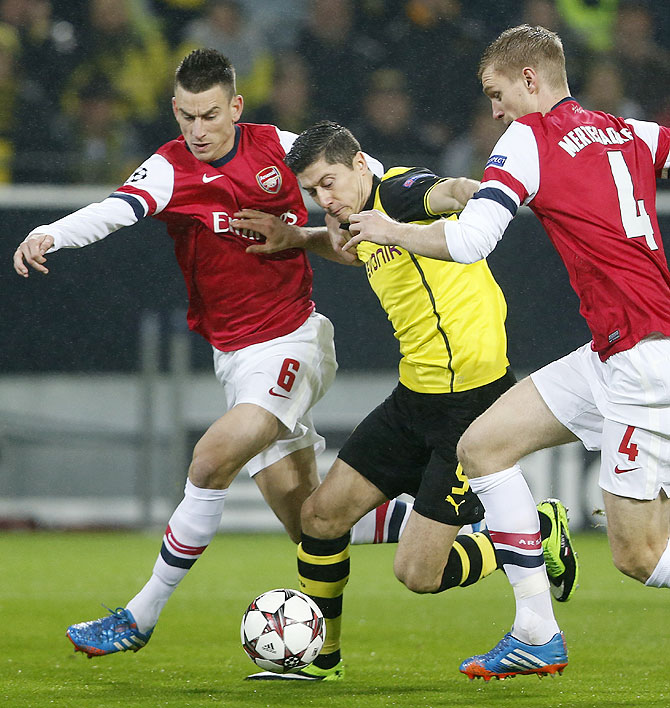 Borussia Dortmund's Robert Lewandowski is challenged by Arsenal's Laurent Koscielny (left) and Per Mertesacker (right) during their Champions League Group F match in Dortmund on Wednesday