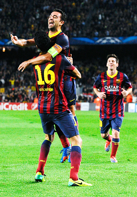 Sergio Busquets (left) of FC Barcelona celebrates with teammate Xavi Hernandez after scoring his team's second goal during their UEFA Champions League Group H match against AC Milan at Camp Nou in Barcelona on Wednesday