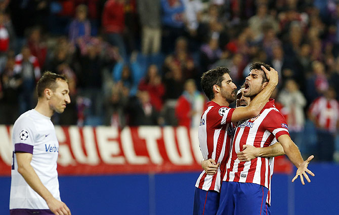 Atletico Madrid's Diego Costa celebrates with teammates Raul Garcia (left) and Juan Francisco Torres Juanfran (center) after scoring against Austria Vienna during their Champions League Group G match at Vicente Calderon stadium in Madrid on Wednesday