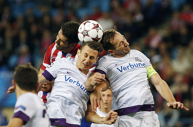 Atletico Madrid's Raul Garcia (left) fights to head the ball with Austria Vienna's Florian Mader (centre) and Manuel Ortlechner during their Champions League Group G match at Vicente Calderon stadium in Madrid on Wednesay