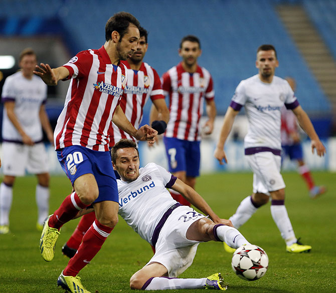 Atletico Madrid's Juan Francisco Torres Juanfran (left) and Austria Vienna's Marin Leovac vie for possession during their Champions League Group G match at Vicente Calderon stadium in Madrid on Wednesday