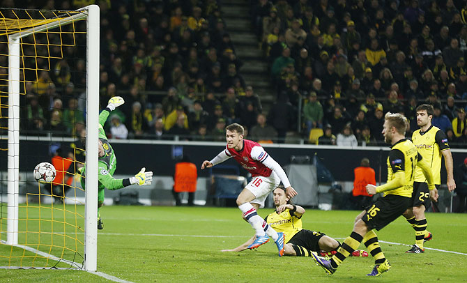 Arsenal's Aaron Ramsey (centre) scores a goal past Borussia Dortmund's goalkeeper Roman Weidenfeller during their Champions League Group F match in Dortmund on Wednesday