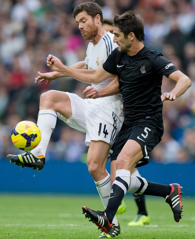 Xabi Alonso (left) of Real Madrid CF competes for the ball with Markel Bergara (right) of Real Sociedad