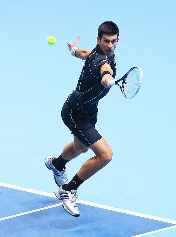 Novak Djokovic of Serbia hits a backhand in his men's singles semi-final match against Stanislas Wawrinka of Switzerland during their match at the ATP World Tour Finals at O2 Arena in London on Sunday