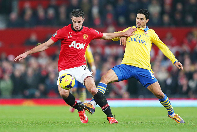 Robin van Persie of Manchester United and Mikel Arteta of Arsenal fight for possession during their Premier League match at Old Trafford in Manchester on Sunday