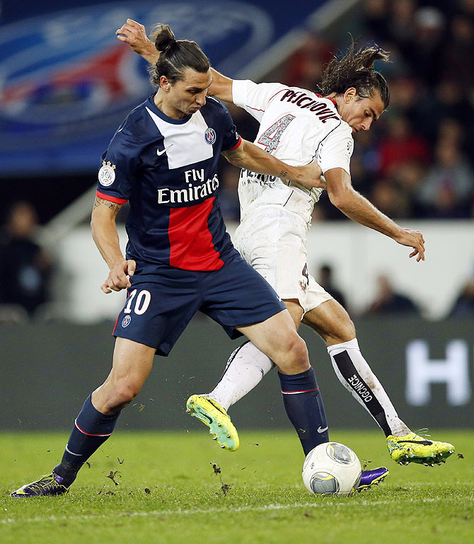Paris St Germain's Zlatan Ibrahimovic (left) challenges Nice's Nemanja Pejcinovic during their French Ligue 1 soccer match at the Parc des Princes Stadium in Paris on Saturday