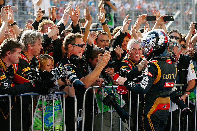 Romain Grosjean of France and Lotus celebrates with his team after finishing second in the United States Formula One Grand Prix at Circuit of The Americas in Austin, Texas on Sunday