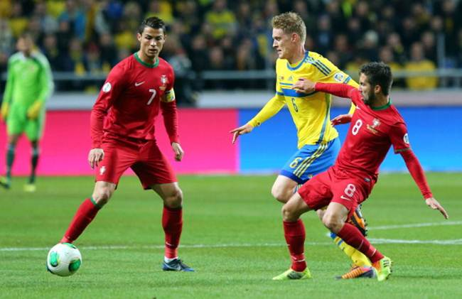Rasmus Elm (centre) of Sweden battles for the ball with Ronaldo (No 7) and Joao Moutinho (No 8)
