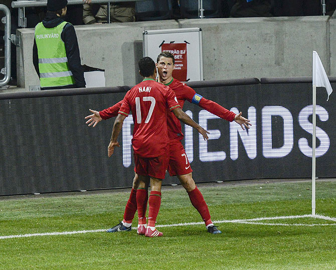 Portugal's Cristiano Ronaldo celebrates his goal with teammate Nani during their second leg of their 2014 World Cup qualifying against Sweden at Friends Arena in Stockholm on Tuesday