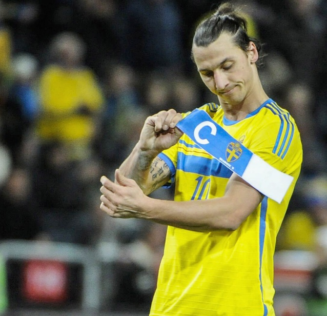 Sweden's forward Zlatan Ibrahimovic takes off the captain's armband after losing their 2014 World Cup qualifying match to Portugal