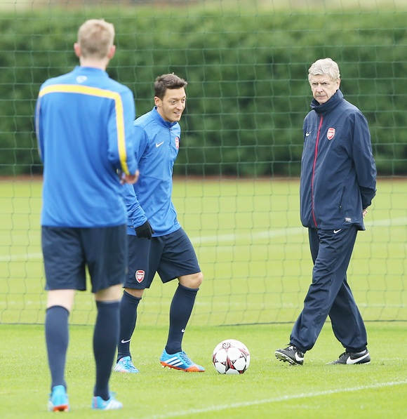 Mesut Oezil speaks to Arsenal manager Arsene Wenger