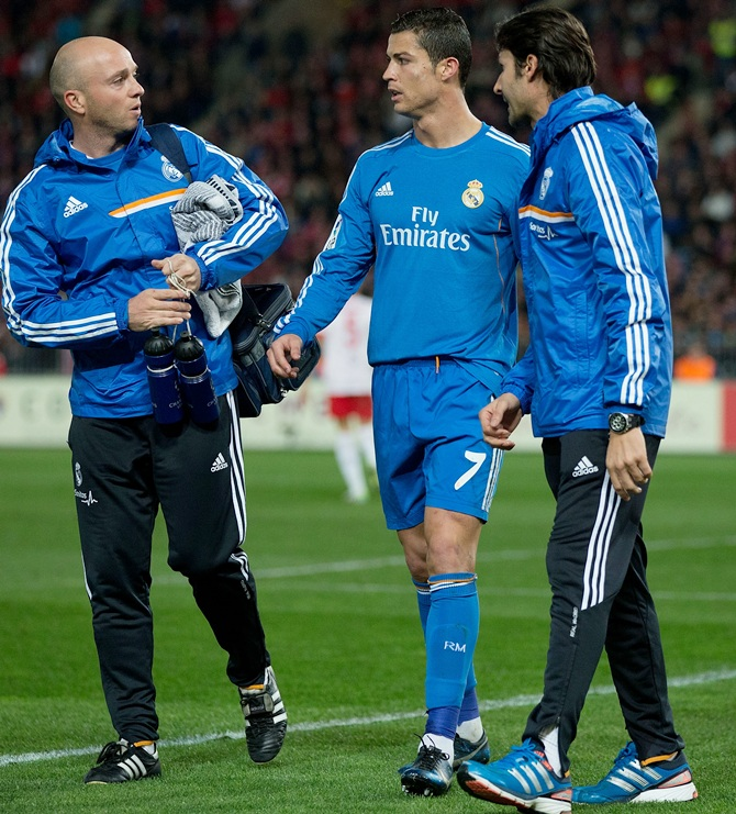 Cristiano Ronaldo of Real Madrid CF leaves the pitch after a pain surrounded by Real Madrid medical staff