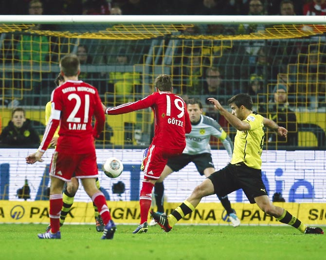 Bayern Munich's Mario Goetze (centre) scores against Borussia Dortmund
