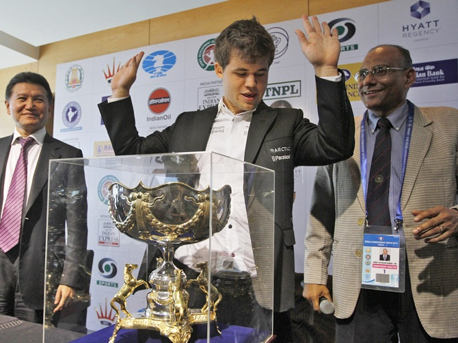 Norway's Magnus Carlsen (centre) gestures next to his trophy after clinching the FIDE World Chess Championship in Chennai