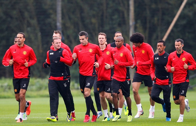 Manchester United players warm up during a training session