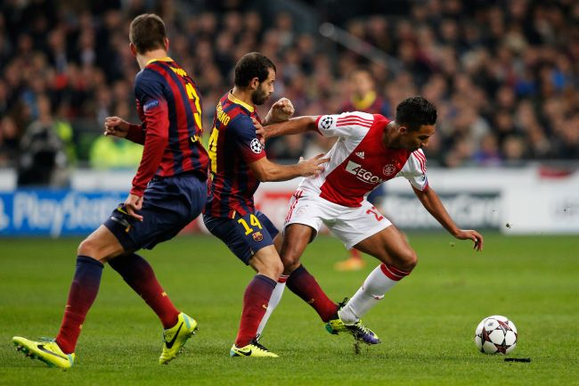 Danny Hoesen of Ajax battles for the ball with Javier Mascherano and Gerard Pique of Barcelona