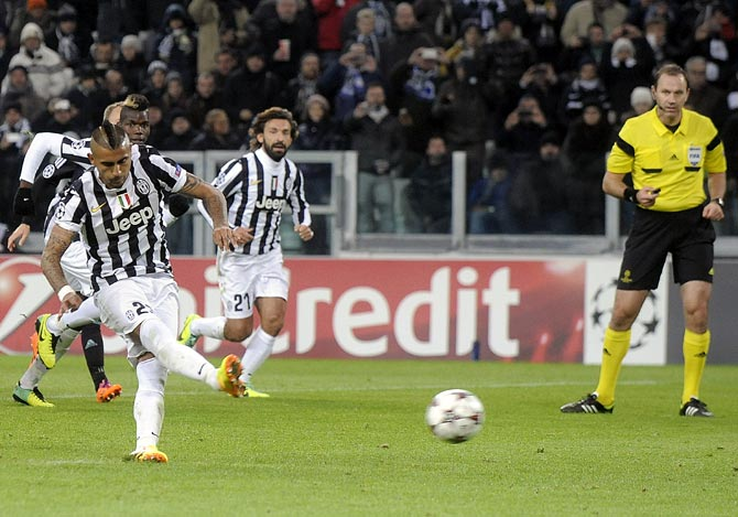 Arturo Vidal of Juventus shoots to score a penalty against FC Copenhagen