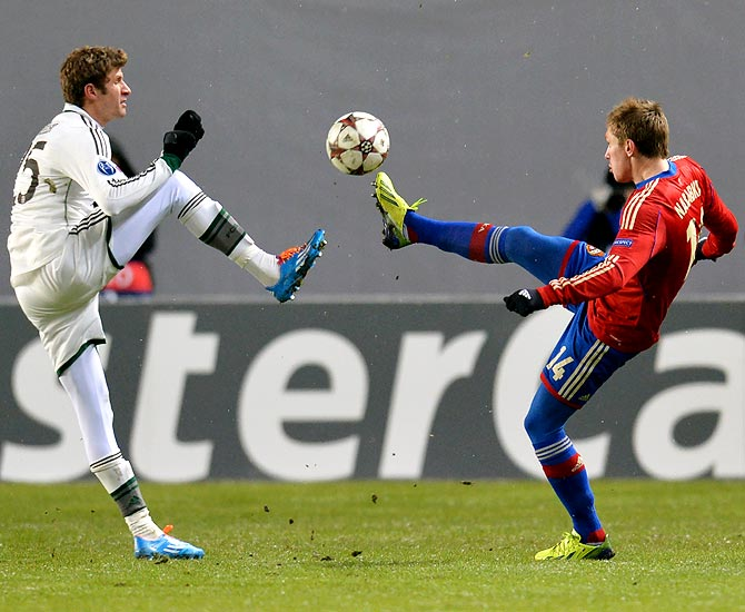 Thomas Muller of Bayern Munich tries to get the ball past Kirill Nababkin (right) of CSKA Moscow