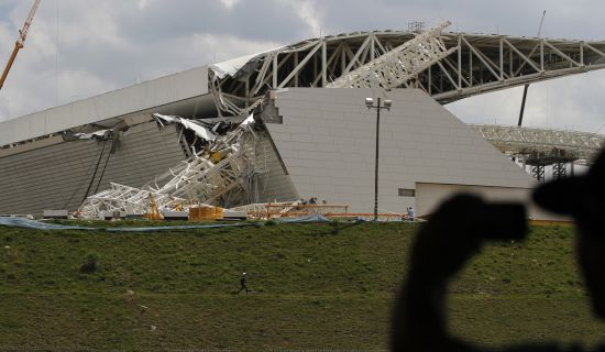 A man takes a picture of a crane that collapsed on the site of the Arena Sao Paulo stadium