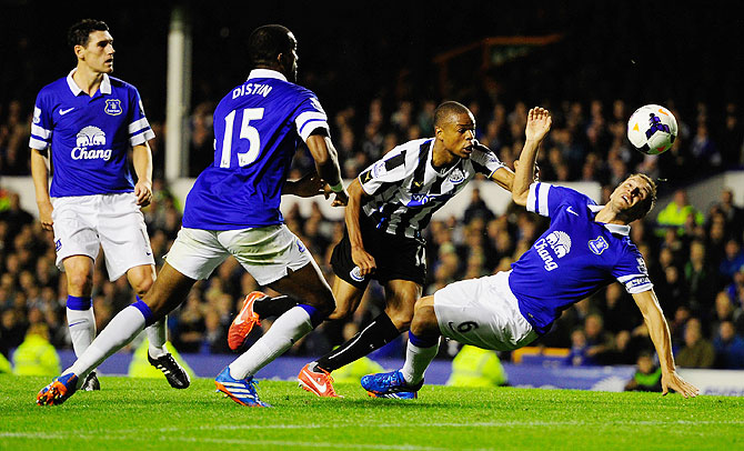 Newcastle player Loic Remy beats Phil Jagielka to score the second newcastle goal against Everton during their Premier League match at Goodison Park on Monday