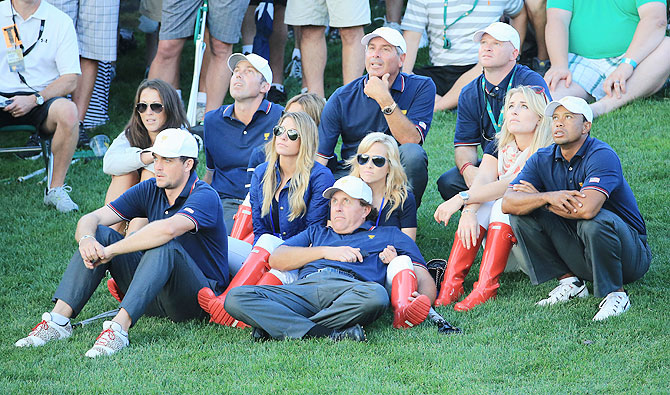 Tiger Woods of the U.S. Team watches the play with his temmates and their partners during the Day One Four-Ball Matches of the Prsident's Cup at the Muirfield Village Golf Club in Dublin, Ohio, on Thursday