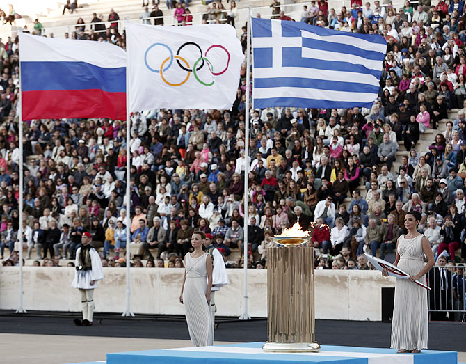 Greek actress Ino Menegaki (right), playing the role of high priestess, stands next to an altar during a handover ceremony of the Olympic flame for the Sochi 2014 Winter Games at the Panathenean stadium in Athens on Saturday