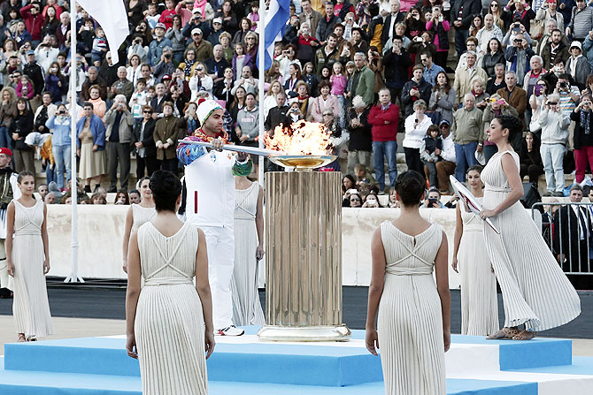 Greek figure skater Panagiotis Markouzios lights an altar with an Olympic torch of the Sochi 2014 Winter Games during a handover ceremony at the Panathenean stadium in Athens on Saturday
