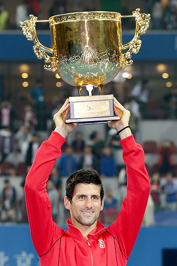 Novak Djokovic of Serbia poses celebrates with the trophy after defeating Rafael Nadal of Spain during the final of the 2013 China Open at the National Tennis Center in Beijing, on Sunday