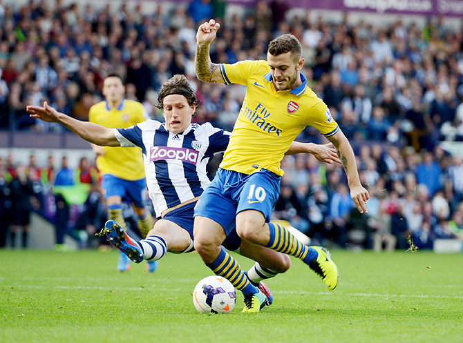 Jack Wilshere of Arsenal is challenged by Billy Jones of West Bromwich Albion during their English Premier League match at The Hawthorns in West Bromwich on Sunday