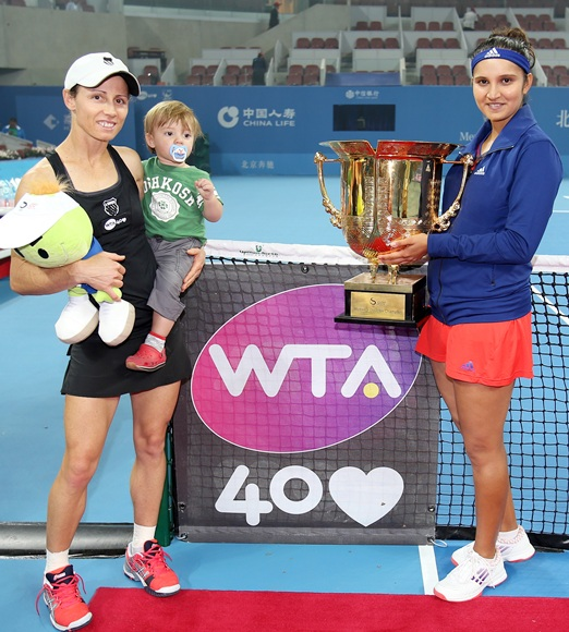 Cara Black of Zimbabwe, holding her son Lachlan, and Sania Mirza