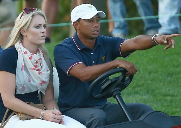Skiier Lindsey Vonn waits with Tiger Woods