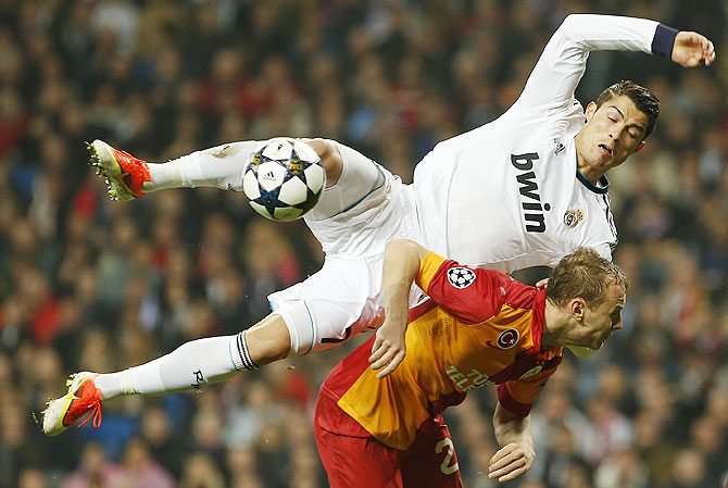 Real Madrid's Cristiano Ronaldo is challenged by Galatasaray's Semih Kaya during a Champions League match