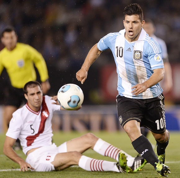 Sergio Aguero (right) of Argentina vies for the ball with Gianmarco Gambetta of Peru