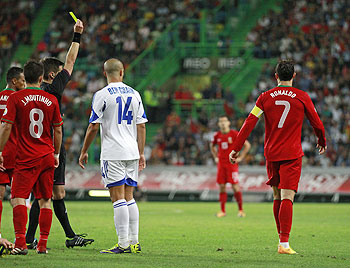 Portugal's Cristiano Ronaldo (R) receives a yellow card from the referee during the match against Israel