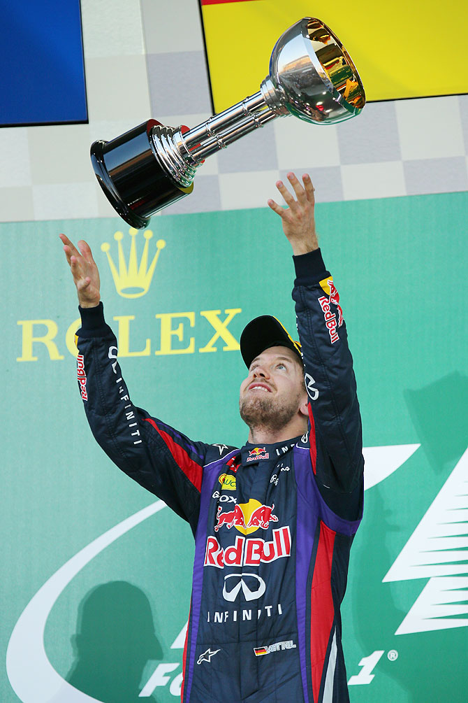 Sebastian Vettel of Germany and Infiniti Red Bull Racing celebrates on the podium after winning the Japanese Formula One Grand Prix at Suzuka Circuit on Sunday
