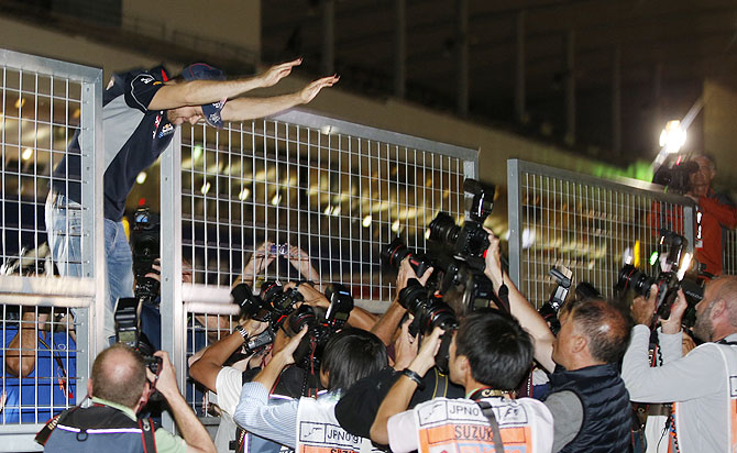 Red Bull Formula One driver Sebastian Vettel of Germany waves to fans after winning the Japanese F1 Grand Prix at the Suzuka circuit on Sunday