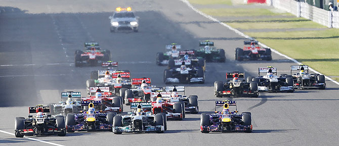 Lotus' Romain Grosjean (left), Red Bull's Mark Webber (right), Mercedes' Lewis Hamilton and Red Bull's Sebastian Vettel fight for the first position during the Japanese F1 Grand Prix at the Suzuka circuit on Sunday