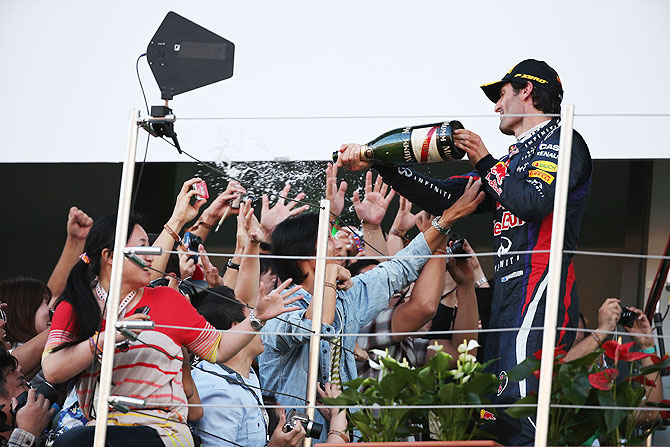 Mark Webber of Red Bull Racing sprays champagne on members of the public in the grandstand after finishing second during the Japanese Formula One Grand Prix at Suzuka Circuit on Sunday