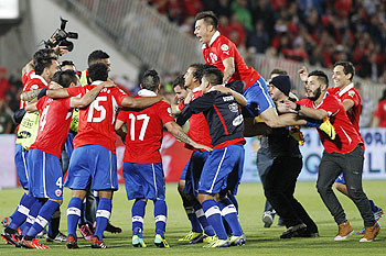 Players of Chile celebrate after defeating Ecuador to qualify for the 2014 World Cup