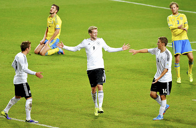 Germany's Andre Schuerrle (centre) celebrates his goal against Sweden with teammates Mario Goetze (L) and Max Kruse while Sweden's Per Nilsson (2nd from left) and Mikael Antonsson react during their 2014 World Cup qualifying match at Friends Arena in Stockholm on Tuesday
